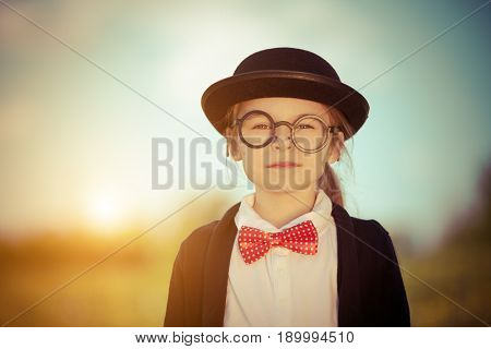 Funny little girl in bow tie and bowler hat. Retro stile.