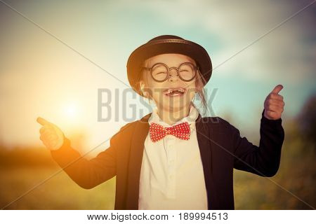 Funny little girl in bow tie and bowler hat showing thumbs up. Retro stile.