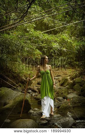 Pacific Islander woman walking in rocky creek