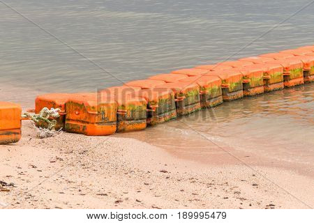 Close up line of dirt sea buoys fasten on sea beach marine equipment for marking safety zone.