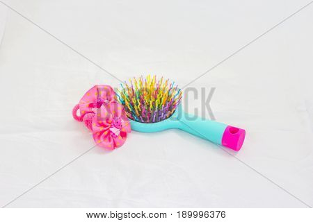 Bright children's Massage hairbrush with hairpins on a white background