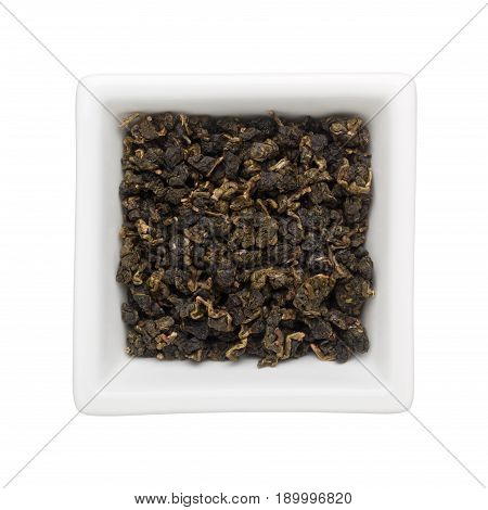 Oolong tea leaves in a square bowl isolated on white background