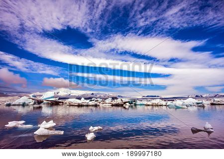 The luminous ice floes and cirrocumulus clouds of lagoon Jokulsarlon, Iceland. The concept of northern extreme tourism. Striped clouds and smooth water of lagoon