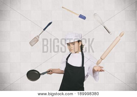 Six years cook girl juggling with some kitchen elements.