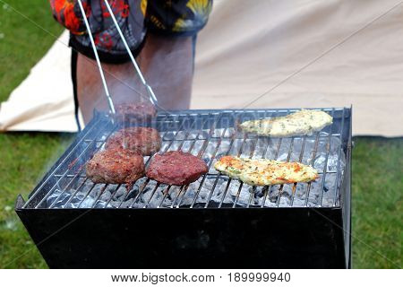 Chicken And Beefburgers Cooking On A Traditional Lumpwood Charcoal Barbecue