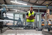 Attentive factory worker maintaining record on clipboard in factory poster