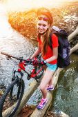 Bicycle teen with ladies bikes in summer park. Woman road bike for running on nature. Teenager girl in helmet cycling fording throught water . Cycling trip is good for health outdoor. Background poster