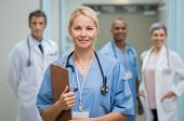 Portrait of a smiling young nurse holding clipboard at hospital. Satisfied female nurse outside operation theatre holding clipboard. Proud female doctor in scrubs looking at camera. poster