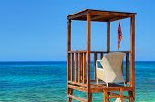 View on wooden beach rescue man place house cabin tower lifeguard on blue sea sand. Rescuer loge chair and flag. Mediterranean Sea, tropical holidays vacations tours poster