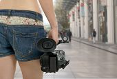 a cameraman girl holding his professional camcorder in the street poster