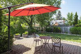 Backyard Garden with Bright Orange Cantilever Umbrella and Bistro Set