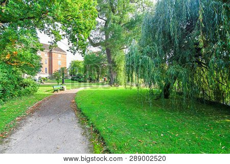A Cement Walking Path Meaders Through A Grassy Lawn With Large Willow And Oak Trees In Shrewsbury, S