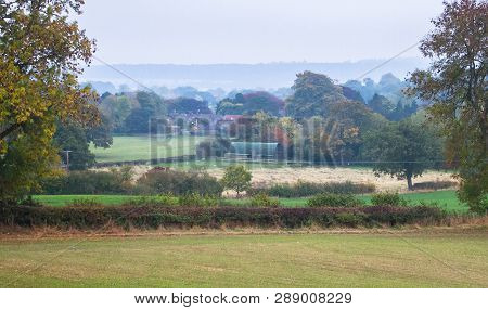 An Idyllic Scene Of Country Houses And Agricultural Land For Sheep Grazing Obscured By Gentle Fog In