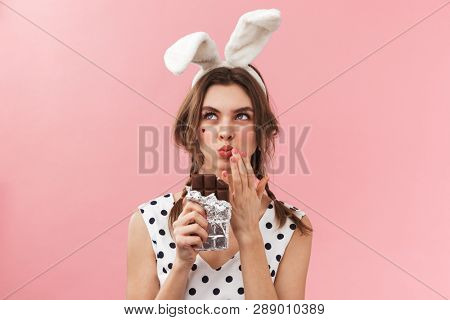 Portrait of a pretty lovely girl wearing bunny ears standing isolated over pink background, eating chocolate