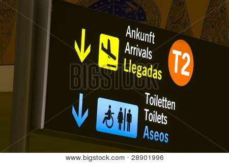 Arrivals and toilets sign panels in airport, Malaga. poster