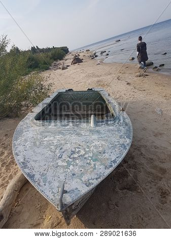 Rybinsk Reservoir Shore With A Boat On The Shore And A Fisherman From The Back, Yaroslavl Region, Ru