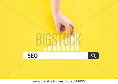 Search Bar With Seo Word And Hand On Chart. Seo Optimization Concept
