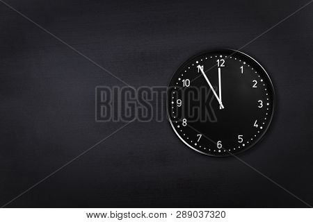 Black Clock Showing Five Minutes To Midnight On Black Chalkboard Background. Office Clock Showing 5