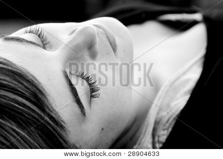 Laying woman with closed eyes, black and white.