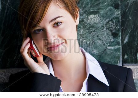Beautiful businesswoman at phone over marble background.