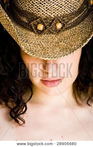 Young curly nude woman with hat.