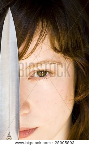 Young blond woman with a knife over her face