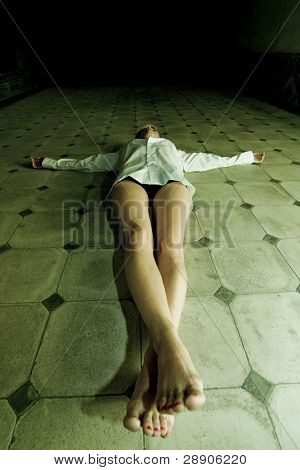 Young seminude crucified woman on the floor