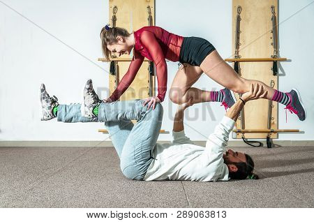 Young Healthy Yoga Fitness Acrobatic Couple Having Fun In The Gym Performing And Practicing Funny Ac