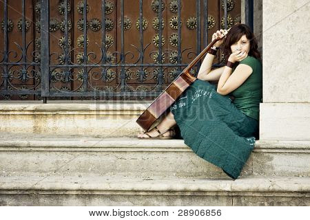 Young female guitarist begging at the church entrance