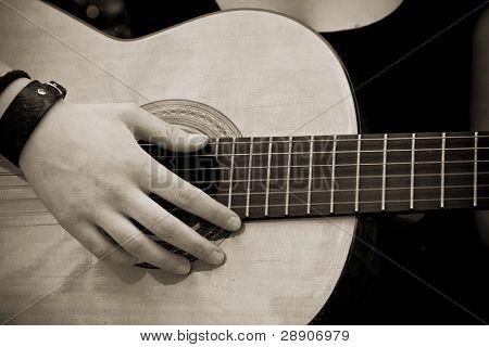 De la mano a la guitarra, sepia antiguo entonado.