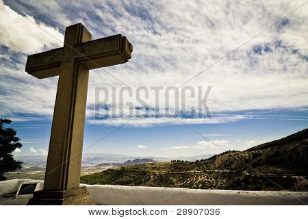 Christian cross in Mediterranean landscape, dramatically toned.