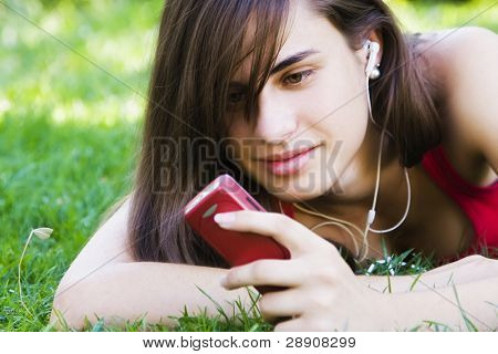 Young woman using her phone at the park.
