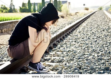 Young sad woman sitting in a railroad
