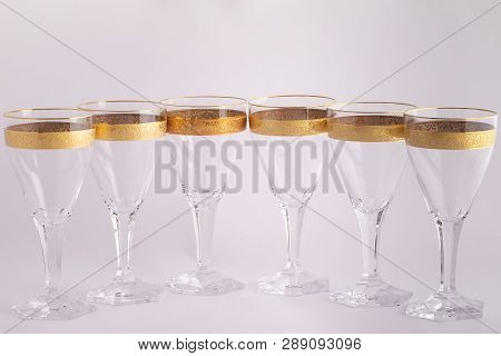 Stemware Glasses Made Of Czech Glass With A Golden Ornament Isolated On A White Background.