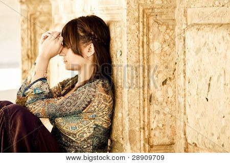 Young worried woman against old stone wall