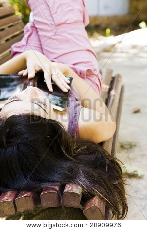 Young woman sleeping in a bench after reading a book.