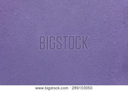 Purple painted stucco wall on Burano Island in the Venetian Lagoon near Venice, Italy. Background texture.