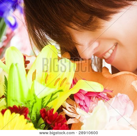 Young smiling woman enjoying a bouquet fragrance. Squared composition.