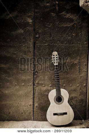 Classic guitar on old door, sepia toned.