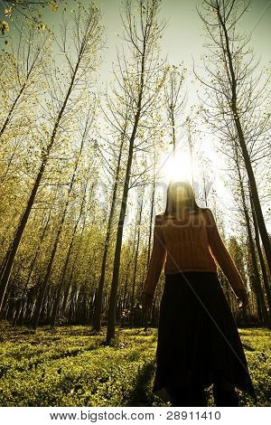 Young woman playing with the sun in the woods