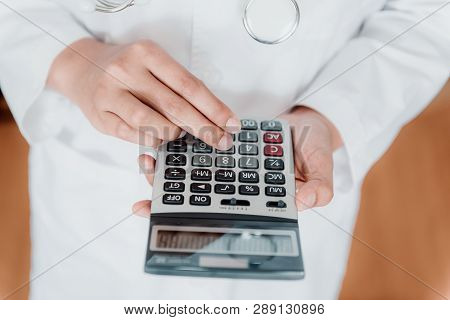 Close-up Of Female Doctor Is Calculating Medicine Cost In Office Hospital, Female Medical Is Using C
