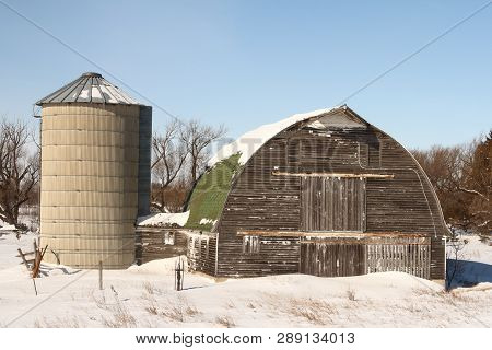 An Old Abandoned Barn And Silo Against A Blue Sky.