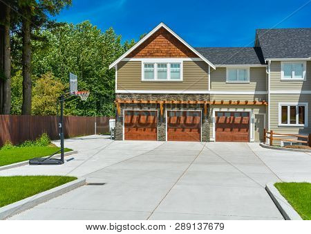Brand New Big Farmer's House With Three Garage Door And Blue Sky Background