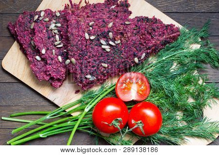 Raw Foods. Dry Vegan Bread Loaves From Beet And Walnut On Kitchen Board On Wooden Table.