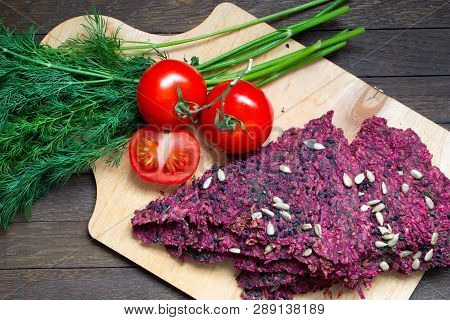 Raw Foods. Vegan Dry Bread Loaves, Tomatoes And Dill On Kitchen Board On Wooden Table