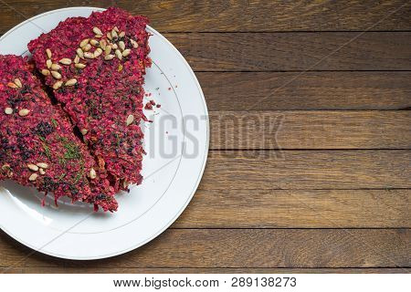 White Plate With Beetroot Vegan Dry Bread Loaves On Wooden Table