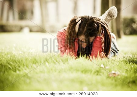 Young sad woman in sad expression over the grass