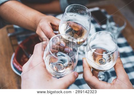 Friends Toasting With Wine At A Bar Outdoors