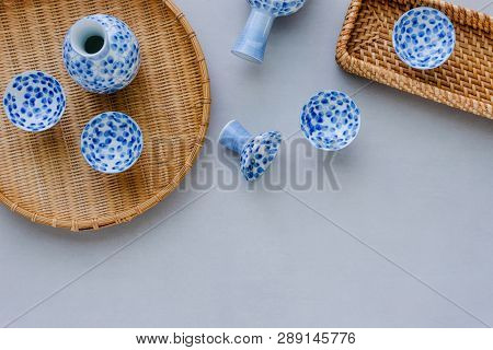 Sake Bottle And Cup On Table Background. Top View
