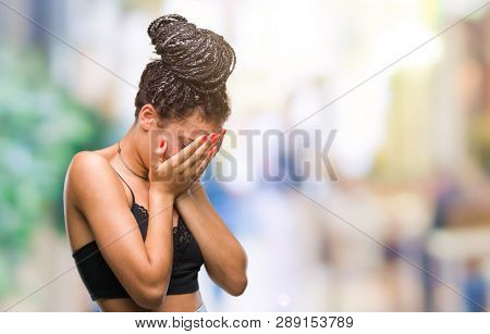 Young braided hair african american with pigmentation blemish birth mark over isolated background with sad expression covering face with hands while crying. Depression concept.